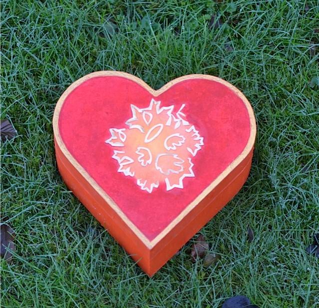 Gedenkdoosje hartvormig. De bovenkant van de gedenkdoos is beschilderd en met uitgezaagde bloemvormen versierd.