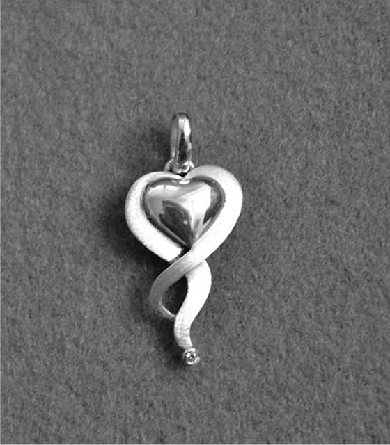 Zilveren, hartvormige hanger waarin de as van een dierbare overledene is verwerkt.