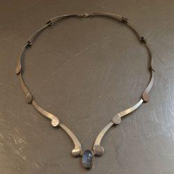 Ketting met maansteen. Zilveren ketting met matte en gepolijste stukken. In het midden een maansteen die eraf geschoven kan worden.