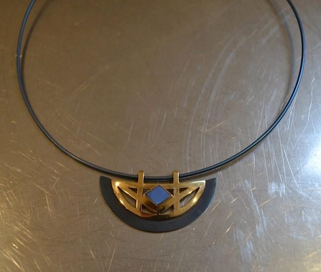Spang met hanger. Gouden hanger met gekleurd titanium.